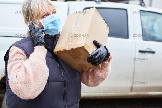 Lieferservice Paketbotin mit Mundschutz ruft Empfänger an