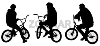 Silhouettes of tree teenagers sitting on bicycles