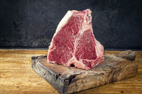 Raw dry aged wagyu porterhouse beef block offered as close-up on black rustic wooden board with copy space
