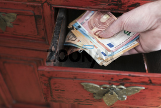 hand taking stack of paper money from drawer