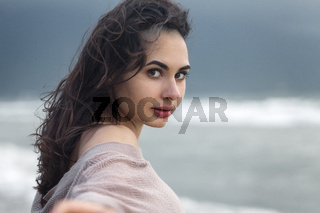 Moody Portrait of Young Woman Have Fun at the Sea Coast Beach with stormy clouds on the sky