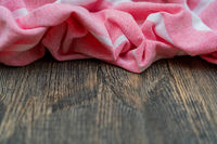 Red and white kitchen towel lies on wooden table. Texture of painted wood. Textured fabric folds.
