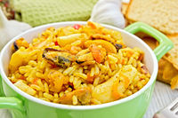 Pilaf with seafood and bread on board