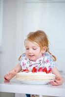 Kind mit frischer Erdbeertorte in Küche