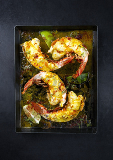 Traditional barbecue spiny lobster tail sliced and offered with saffron lemon sauce as top view on a metal tray with copy space