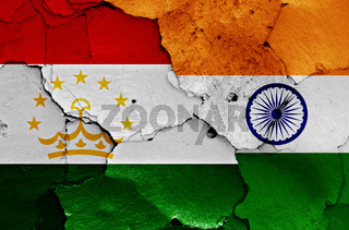 flags of Tajikistan and India painted on cracked wall