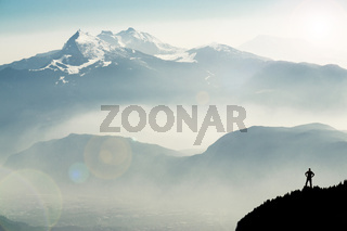 Spectacular mountain ranges silhouettes. Man reaching summit enjoying freedom. View from Top of Mount Corno di Tres, Tresner Horn to Cima Paganella. Trentino, South Tyrol, Alps, Italy.
