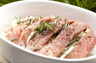 Raw pork meat with fresh herbs and spices.
