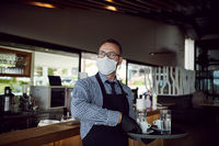 waiter in a medical protective mask serves  the coffee in restaurant