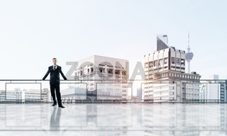 Sunrise above skyscrapers and businessman facing new day