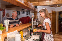 young waitress in dirndl dress serves customers at the counter