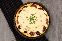 Sheep cheese tart with red onion on wooden background.