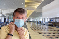 Senior adult man adjusting face mask in airport and looking very worried