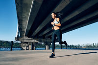 Young fitness woman running at riverside