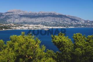 Coastal view to Atea over mediteranean sea and blurred pines in natural park 'Serra Gelada' in Albir, Spain