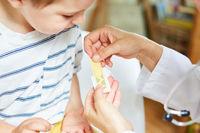 Kind bekommt ein Pflaster auf eine Wunde