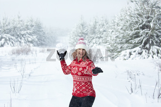 Happy woman throwing a large snowball in winter