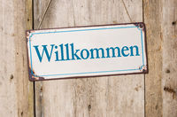 Old metal sign in front of a rustic wooden wall - Welcome - Willkommen German