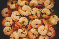 Baby shrimps with parsley and garlic are cooked in a pan, top view, flat lay, close-up