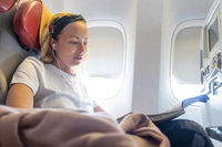 Casual young woman reading magazine and listening to music on airplane. Female traveler reading seated in passanger cabin.