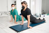 Physiotherapist assisting man in performing exercise on mat