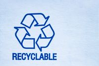 Recyclable symbol on a white cardboard.