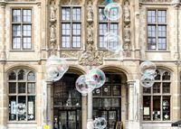 Facade of old post office with soap bubbles in the foreground in Ghent