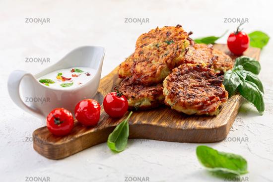 Zucchini fritters with yogurt sauce. Vegetarian cuisine.
