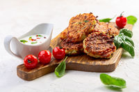 Zucchini fritters with yogurt sauce. Vegetarian cuisine.