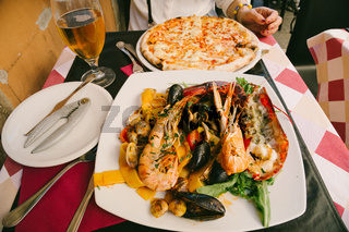 Seafood pasta, pizza and beer in Italy