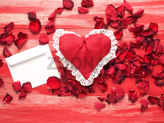 Red fabric heart with a letter and rose petals on wood