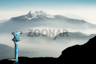 Public binoculars and Mountain Silhouettes at Sunrise. Foresight and vision for new business concepts and creative ideas. Alps, Trentino, South Tyrol, Italy.