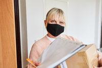 Frau mit Mundschutz vor Wohnung bestätigt Paket Annahme