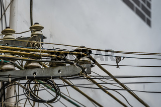 Densely wired telephone and electric cables outside residential buildings