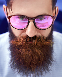 Bearded man in glasses with screen reflection working on computer in IT office, sitting at desk writing code, working on a project in software development company or startup.