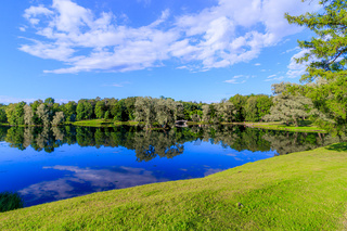 Summer evening in the Park with a lake. Summer landscape. nature of Russia. Well-maintained Park. Evening smoothness. The reflection in the water.