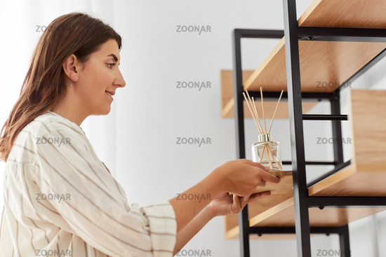 woman placing aroma reed diffuser to shelf home