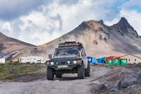 Japanese SUV Nissan Patrol driving on rocky mountain road on background volcanic landscape. Active vacation, off-road trip in travel destinations to volcano