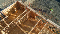 Drone Aerial View of Home Construction Site With Pilot Below