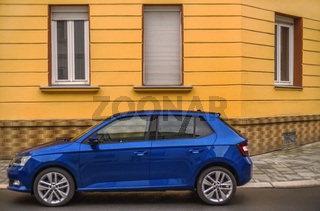 Die Farben Gelb-Orange und Blau - ein Auto vor dem Haus