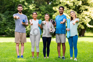 group of happy people with yoga mats at park