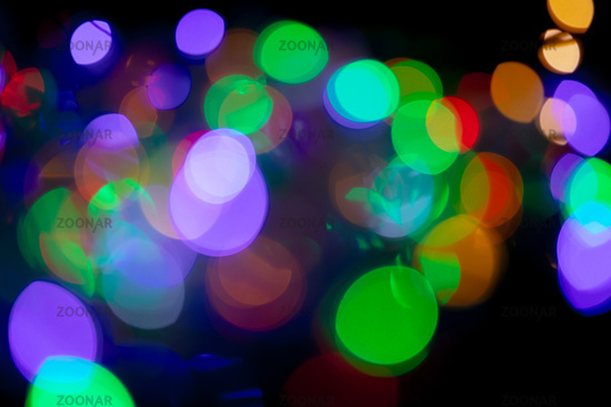 Multicolored spots of light against black background