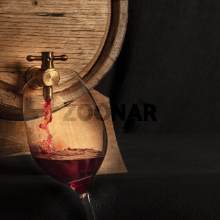 Oak barrel with a glass of red wine, pouring and tasting at a winery cellar, square image with a place for text