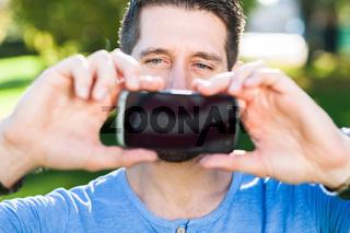 Mann mit Smartphone macht Foto