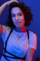 Woman corrects her hair looking at camera on blue background while posing in neon studio lighting. High quality photo
