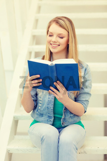 smiling teenage girl reading book