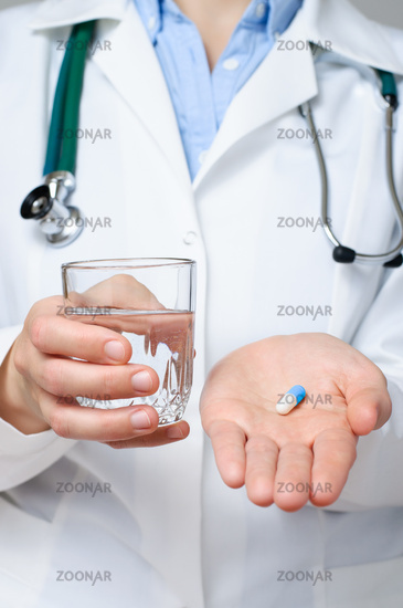 Doctor holding a glass of water and a pill