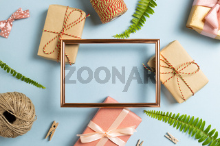 Gift wrapping concept. Empty photo frame with gift boxes on sky blue background. top view, copy space