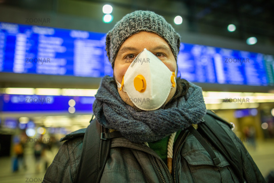 Man wearing a respirator mask device for health protection at an airport or railway train station in
