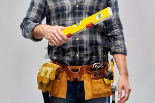 male builder with level and working tools on belt
